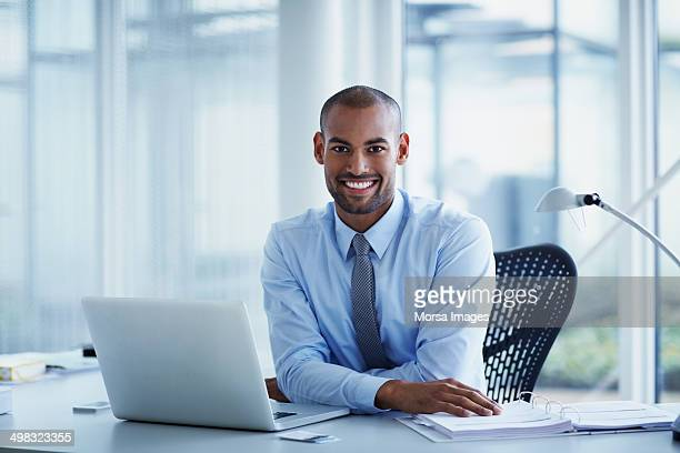 Portrait of happy businessman at desk