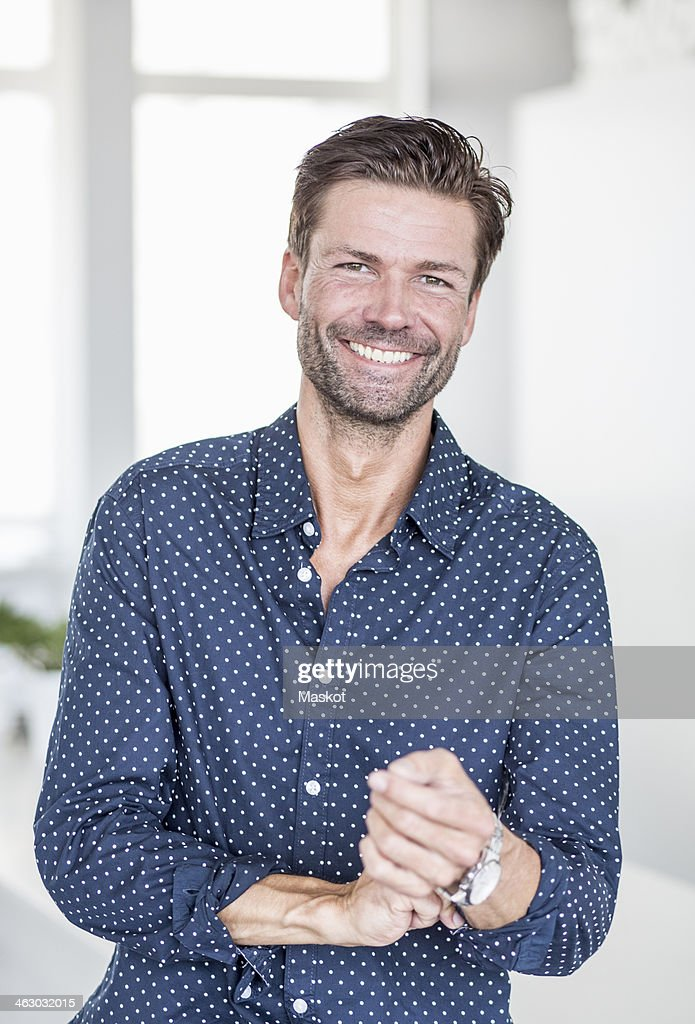 Portrait of happy businessman rolling up shirt sleeves in office