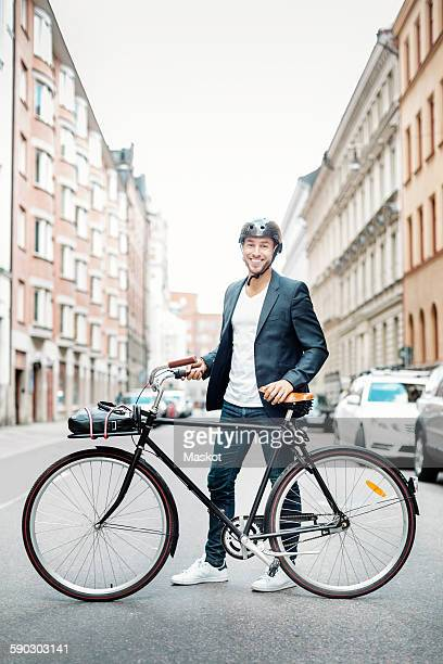 Portrait of happy businessman with bicycle standing on city street