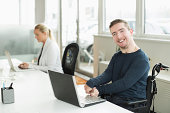 Portrait of happy businessman with cerebral palsy using laptop in office
