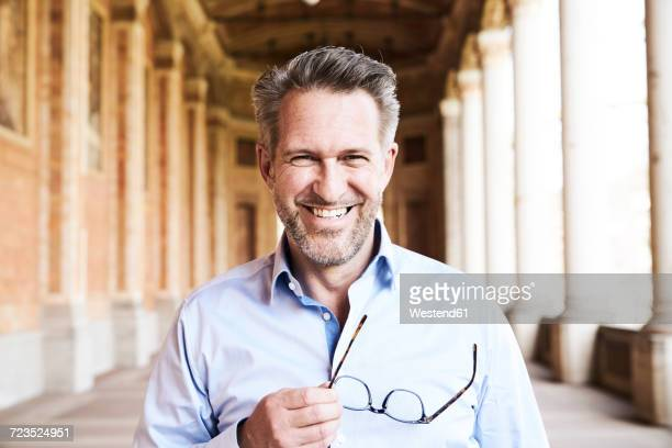 Portrait of happy businessman with stubble wearing glasses