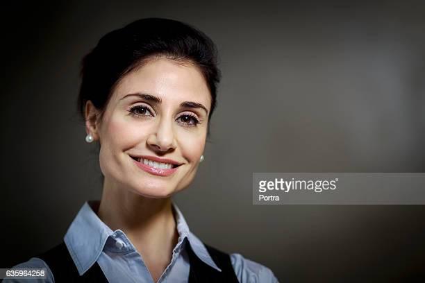 Portrait of happy businesswoman against grey wall