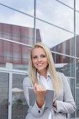 Portrait of happy businesswoman holding digital tablet against office building