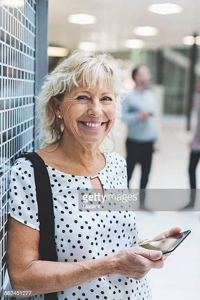 Portrait of happy businesswoman holding digital tablet while leaning on wall in office