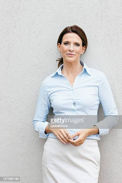 Porträt von glücklichen Geschäftsfrau an eine Wand gelehnt