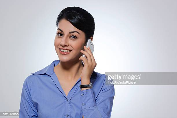 Portrait of happy businesswoman using mobile phone over gray background