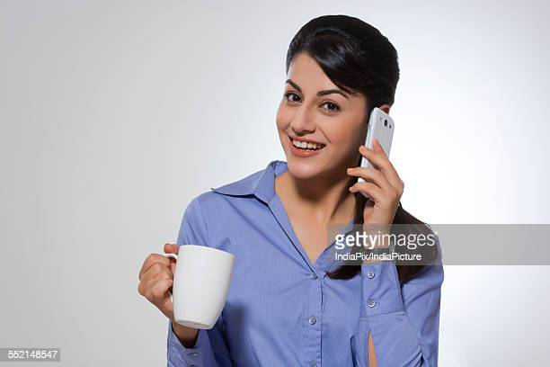 Portrait of happy businesswoman with coffee mug using phone against gray background