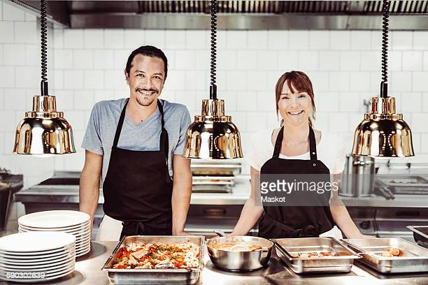 Portrait of happy chefs standing in commercial kitchen counter