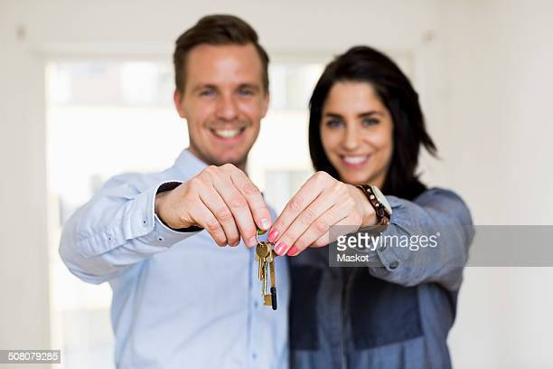 Portrait of happy couple holding keys in new house
