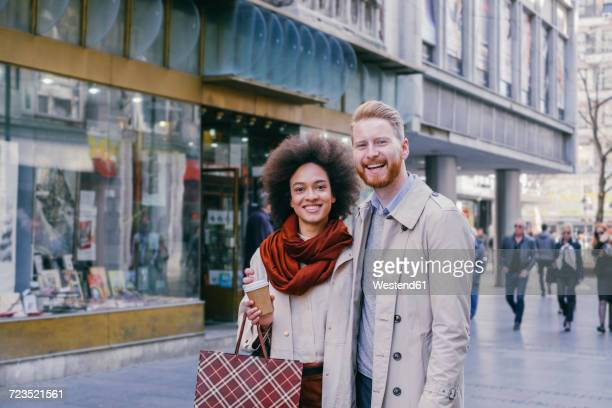 Portrait of happy couple shopping in the city