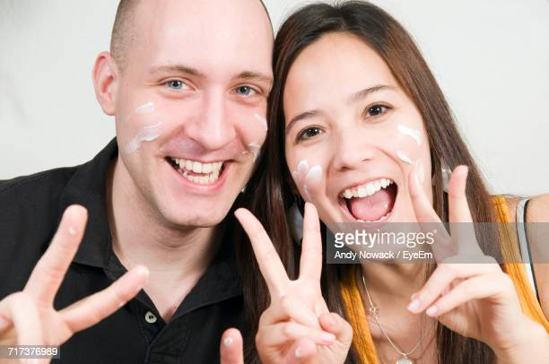 Portrait Of Happy Couple Showing Peace Sign