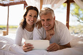 Portrait of happy couple using digital tablet on bed during morning