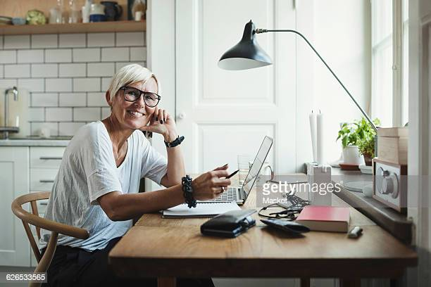Portrait of happy designer sitting at table in home office