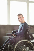 Portrait of happy disabled businessman sitting on motorized wheelchair in office