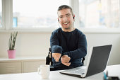 Portrait of happy disabled businessman with laptop at desk in office