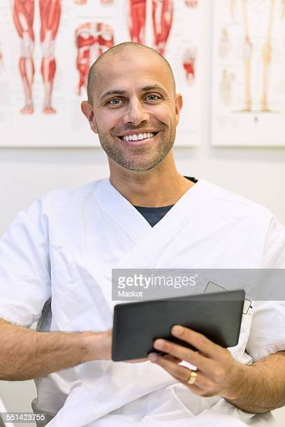 Portrait of happy doctor holding digital tablet in orthopedic clinic