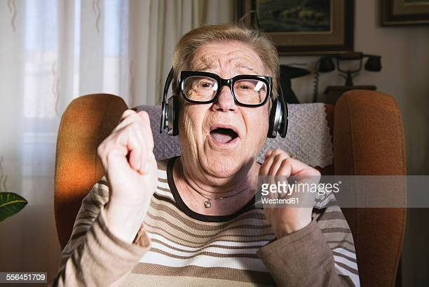 Portrait of happy elderly lady hearing music with headphones