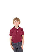 Portrait of happy elementary boy in school uniform over white background