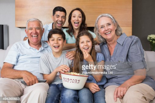 Portrait of happy extended family watching tv in living room : Stock-Foto
