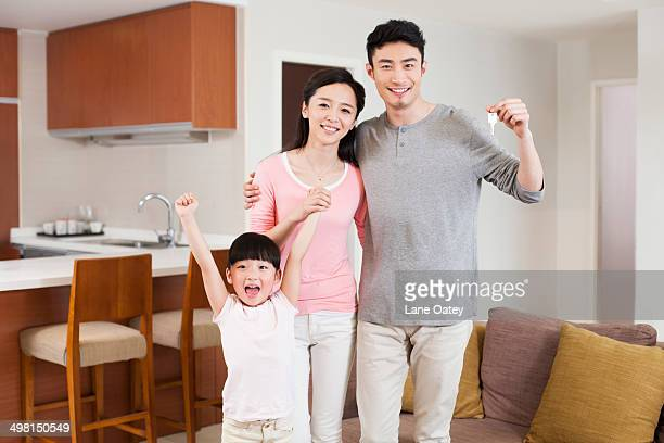 Portrait of happy family cheering with key in hand