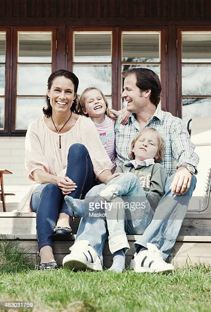 Portrait of happy family of four enjoying in yard