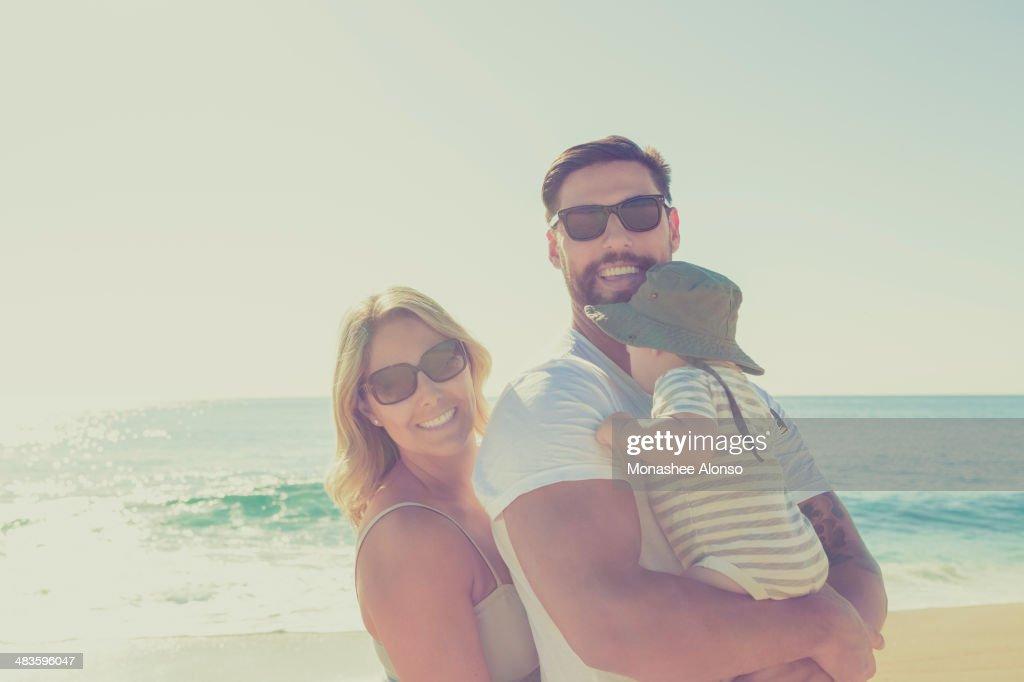 Portrait of happy family on sunny beach
