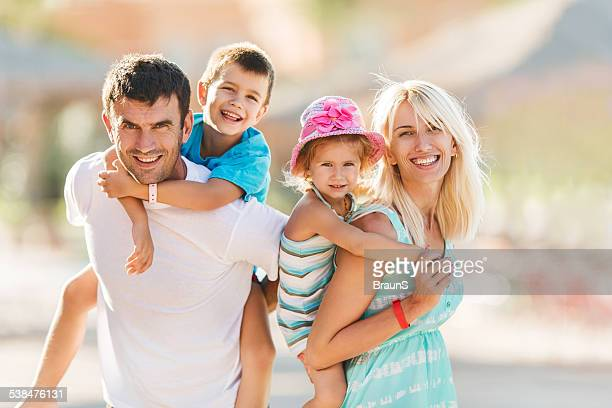 Portrait of happy family piggybacking in summer.