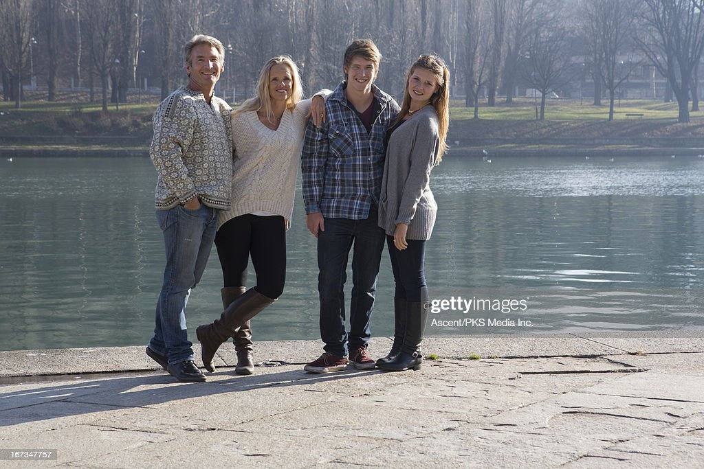 Portrait of happy family standing on river's edge : Stock Photo