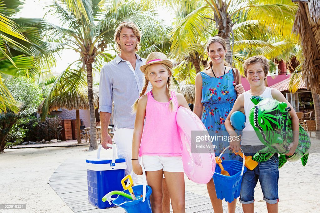 Portrait of happy family with children (10-12) on beach : Stockfoto