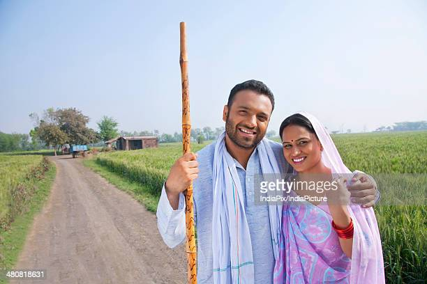Portrait of happy farmer and wife standing in farm