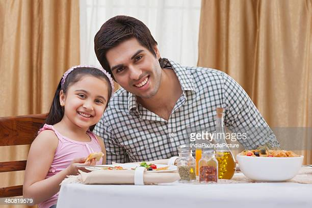 Portrait of happy father and daughter having food at restaurant