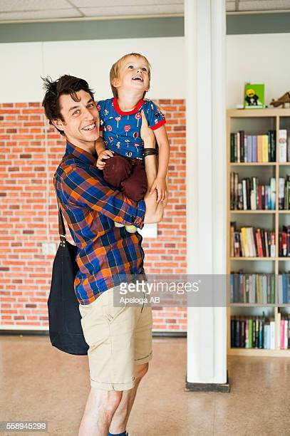 Portrait of happy father carrying son at primary school