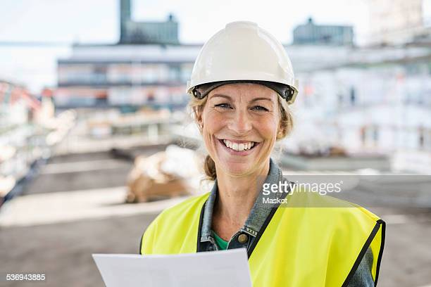 Portrait of happy female architect at construction site