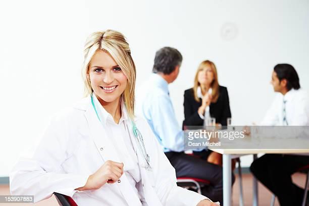 Portrait de heureuse femme médecin avec des collègues derrière
