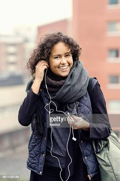 Portrait of happy female university student in warm clothing wearing headphones outdoors