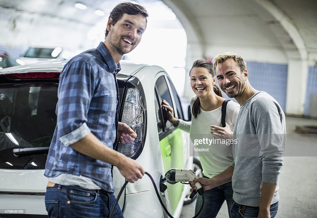 Portrait of happy friends with man charging electric car at gas station : Stock-Foto