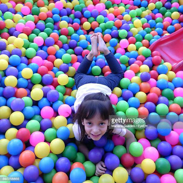 Portrait Of Happy Girl Amidst Colorful Ball Pool At Playground
