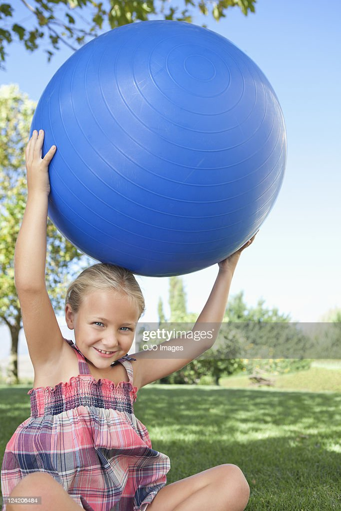 Portrait of happy girl holding fitness ball on top of her head in park : Stock Photo