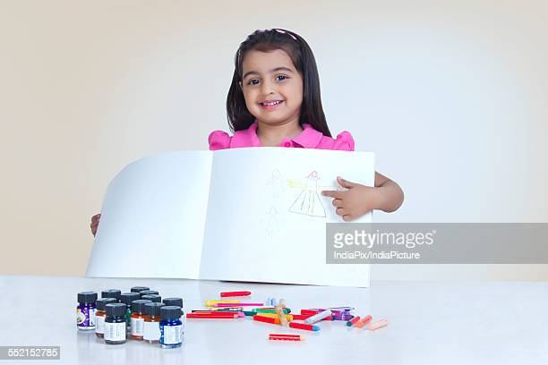 Portrait of happy girl showing drawing against white background