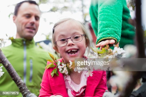 Portrait of happy handicapped girl with father and brother in yard