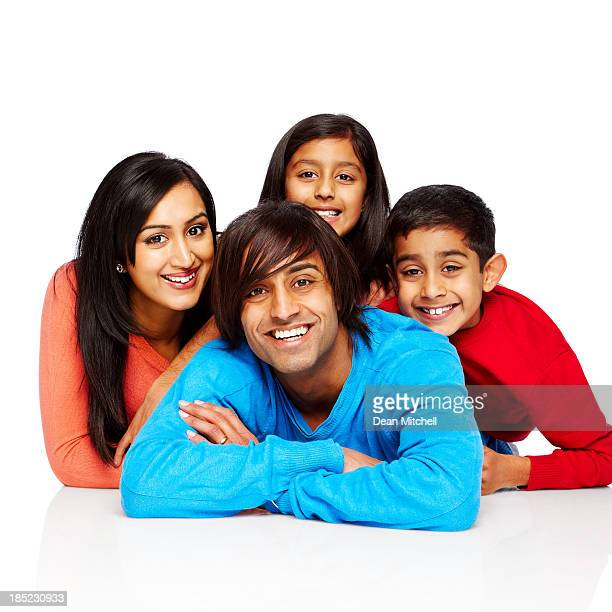Portrait of happy Indian family lying on floor