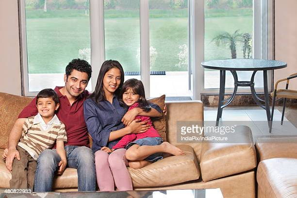 Portrait of happy Indian family of four sitting together on sofa