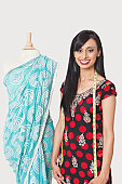 Portrait of happy Indian female fashion designer standing by dummy draped in a sari