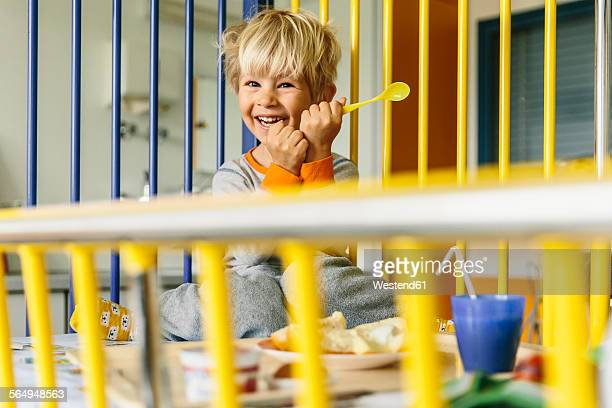 Portrait of happy little boy sitting in childrens hospital bed having breakfast