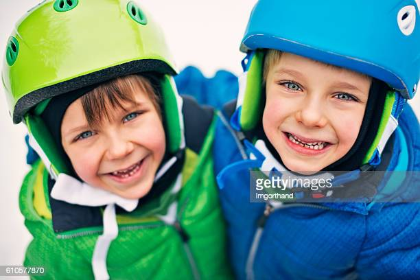 Portrait of happy little boys wearing ski helmets