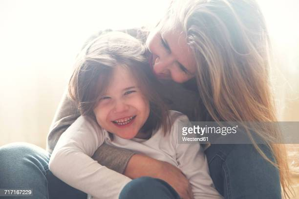 Portrait of happy little girl at home with her mother