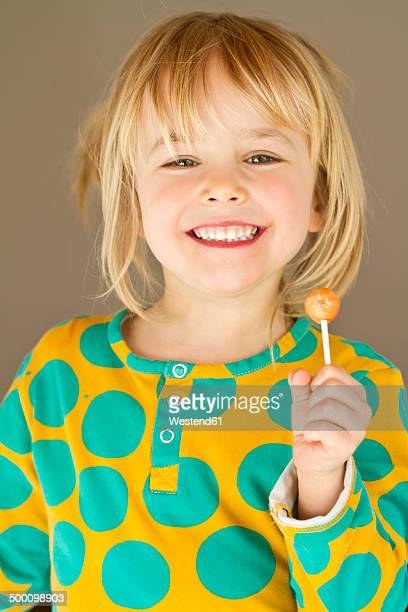 Portrait of happy little girl holding lolly