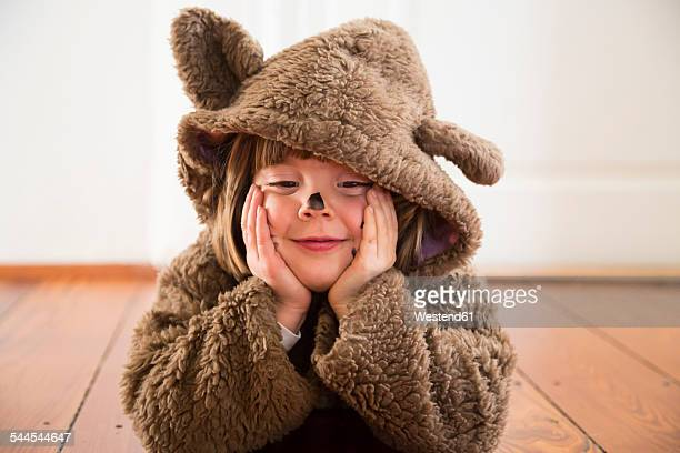 Portrait of happy little girl masquerade as a bear lying on wooden floor