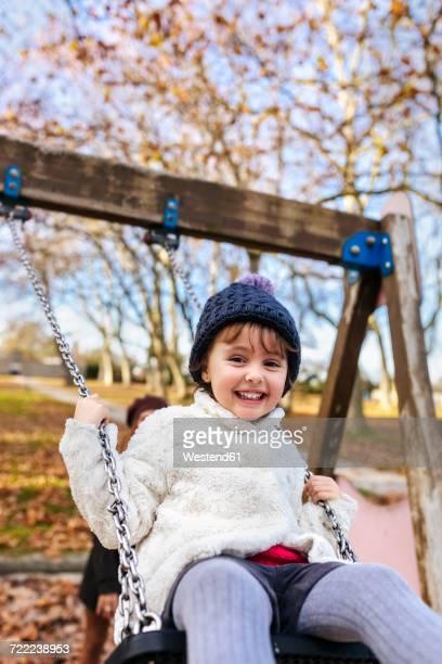 Portrait of happy little girl on a swing