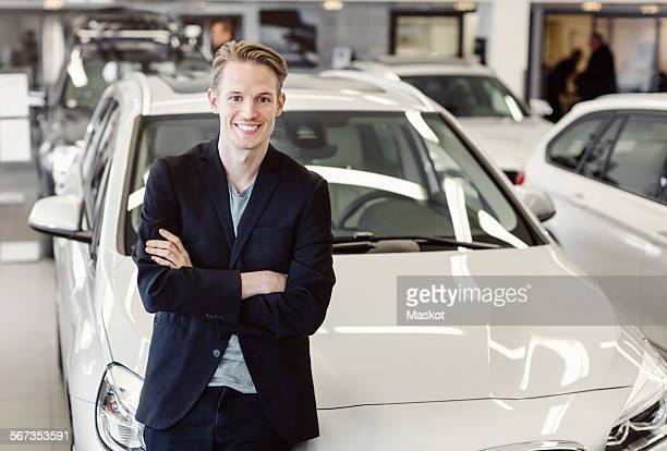 Portrait of happy male customer leaning on car at showroom